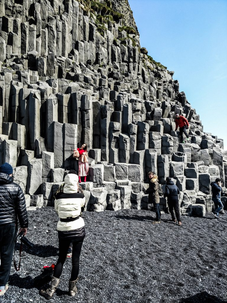 Modern Day Tourists Near Basalt Columns in Iceland